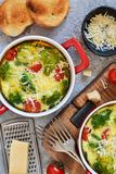 Casserole with broccoli, tomatoes and parmesan on a concrete background. View from above. Casserole with broccoli, tomatoes and parmesan on a concrete background stock images