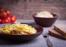 Casserole with cabbage in ceramic dish. Casserole with potato and cabbage in ceramic dish with fork, bread and tomato Stock Photos