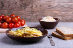 Casserole with cabbage in ceramic dish. Casserole with potato and cabbage in ceramic dish with fork, bread and tomato Stock Photography