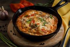 Casserole chaude avec l'omelette et les légumes sur une table en bois image stock