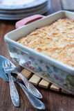 Casserole of cheese in a square shape on a wooden table Stock Photography