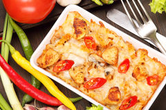 Casserole with chicken and chili peppers on a wooden background Royalty Free Stock Photos