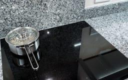 Casserole d'acier inoxydable sur la fraise-mère ou le cooktop moderne d'induction photo libre de droits