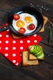 Casserole d'oeufs au plat et de cerise-tomates avec du pain, avocat sur la table en bois foncée Photographie stock