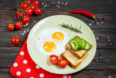 Casserole d'oeufs au plat et de cerise-tomates avec du pain, avocat sur la table en bois foncée Photo libre de droits