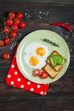 Casserole d'oeufs au plat et de cerise-tomates avec du pain, avocat sur la table en bois foncée Images libres de droits