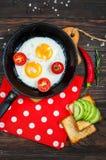 Casserole d'oeufs au plat et de cerise-tomates avec du pain, avocat sur la table en bois foncée, vue supérieure Image stock
