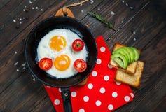 Casserole d'oeufs au plat et de cerise-tomates avec du pain, avocat sur la table en bois foncée, vue supérieure Images stock