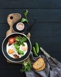 Casserole d'oeufs au plat, lard, tomates avec du pain Photos libres de droits