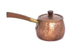 Casserole de cuivre avec une poignée en bois sur le fond blanc Image stock