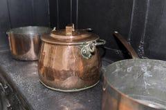 Casserole de cuivre victorienne de cocotte en terre sur une cuisinière à gaz antique noire dans a Images libres de droits