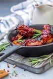 Casserole de fonte avec les nervures de porc cuites au four et le romarin frais image libre de droits