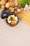 Casserole dish with organic vegetables and herbs on kitchen worktop, copy space, vertical Stock Photo