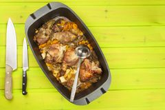 Casserole dish with pork on a wooden board. Homework communal meal. Stock Images