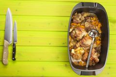 Casserole dish with pork on a wooden board. Homework communal meal. Royalty Free Stock Image