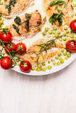 Casserole dish with roasted chicken breast in cream sauce with green pea and tomatoes Royalty Free Stock Images