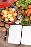 Casserole dish with various organic vegetables and cookbook or recipe book, copy space Stock Photo