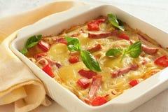 Casserole med ost, bacon och tomater Fotografering för Bildbyråer