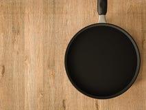 Casserole noire vide sur la table en bois Photographie stock libre de droits
