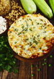 Casserole of pasta with green peas, zucchini and curd Stock Images