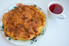 Casserole on a plate with a cup of cranberry compote on a white background. stock images