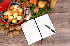 Casserole pot with vegetables and recipe cookbook, copy space, top view Stock Photos