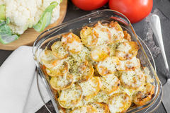 Casserole from potato with sour cream sauce, vegetables and gree Stock Photos