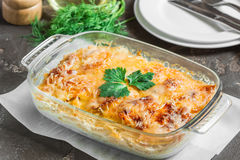 Casserole with potatoes, melted cheese, fresh green apple and le. Potato gratin with cream cheese and fresh herbs Royalty Free Stock Images