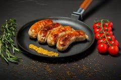 Casserole ronde avec quatre saucisses frites et moutarde granulaire image stock