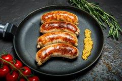 Casserole ronde avec quatre saucisses frites et moutarde granulaire image libre de droits