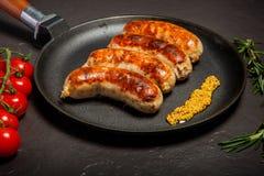 Casserole ronde de plan rapproché avec les saucisses frites et la moutarde granulaire photo stock