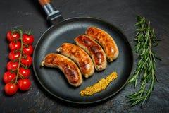 Casserole ronde de vue sup?rieure avec quatre saucisses frites et moutarde granulaire photographie stock