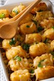 Casserole of Tater Tots with cheese and herbs close up in a dish. Baking dish on the table. vertical Royalty Free Stock Image
