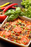 Casserole with tomato and mushrooms on a wooden background Stock Image