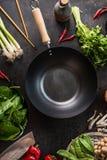 Casserole vide de wok sur la table de cuisine avec des baguettes et des ingrédients de nourriture asiatiques végétariens, vue sup photographie stock