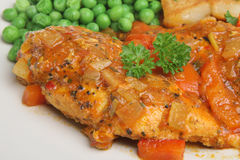Casseroled Chicken Breast. Marinated and casseroled chicken breast in a tomato sauce served with sauteed potatoes and peas Royalty Free Stock Photography