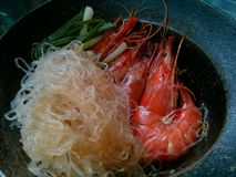 Casseroled prawns or shrimps with glass noodles. Street food in the market Royalty Free Stock Photo