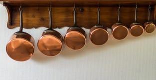 Casseroles accrochant dans la cuisine images libres de droits