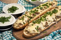 Casseruola con formaggio ed i funghi spruzzati con la erba cipollina fresca immagini stock
