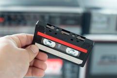 Cassete áudio plástica da gaveta na mão de um homem Imagem de Stock
