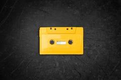 Cassete de banda magnética retro amarela sobre o quadro-negro Vista superior imagens de stock