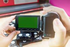 Cassetes de banda magnética da gravação da mão e da câmara de vídeo no backgro do escritório Imagens de Stock