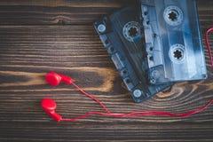 Cassetes de banda magnética e fones de ouvido no fundo de madeira Fotografia de Stock