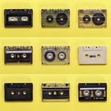 Cassetes de banda magnética retros de música no fundo amarelo Fotos de Stock Royalty Free