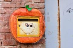Cassetta delle lettere arancio con il sorriso, cassetta delle lettere che appende sulla parete fotografia stock