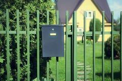 Cassetta delle lettere che appende sul recinto sul fondo vago della casa Fotografia Stock