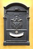 Cassetta delle lettere nera d'annata sulla parete gialla Immagine Stock