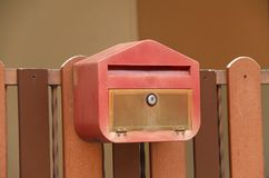 Cassetta delle lettere rossa con il recinto di legno marrone Fotografie Stock Libere da Diritti