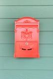 Cassetta delle lettere rossa con legno verde Immagini Stock Libere da Diritti