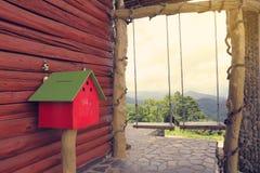 Cassetta delle lettere rossa contro la parete di legno vicino a due oscillazioni sulla collina fotografie stock libere da diritti
